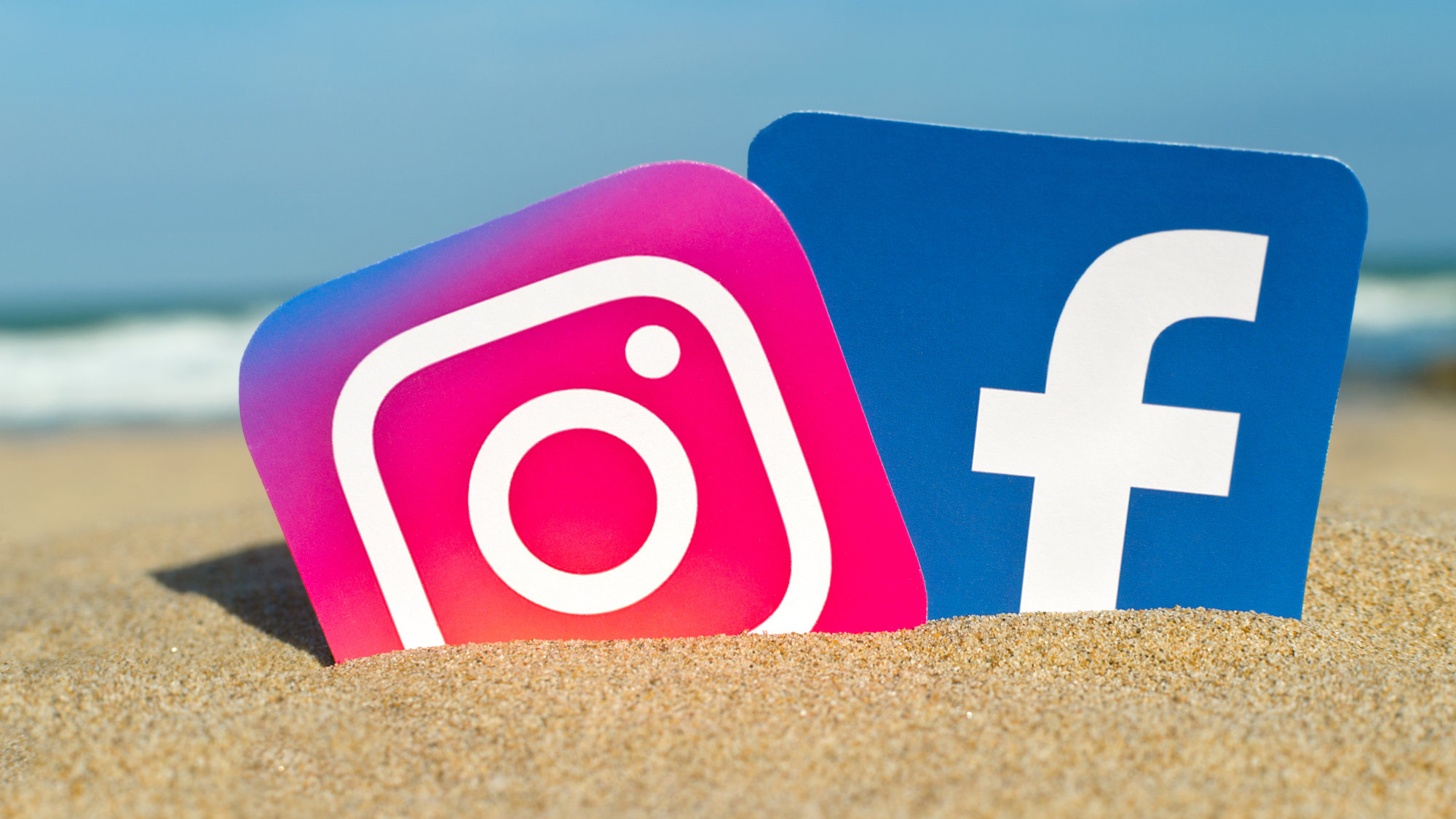 Instagram and Facebook logos dug into the sand