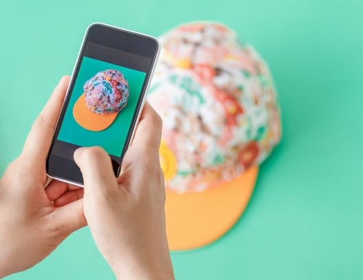 Hands holding a smart phone taking a picture of colorful hat